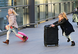 Two excited children rushing to check in at London Gatwick airport as the Christmas getaway starts Friday, 20th December 2013. Picture by Stephen Lock / i-Images