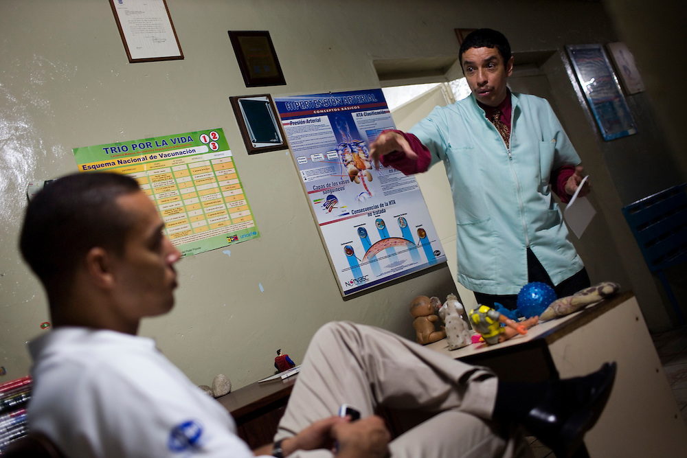 Julio Rodrguez talkes with  Dr. Carlos Serrano, a general practitioner in Petare, one of the largest and most dangerous slums of Caracas.  Pfizer is trying to increase their market share in the slums and are targeting clinics and hospitals, sending sales representatives like Julio to the far reaches of the slum.