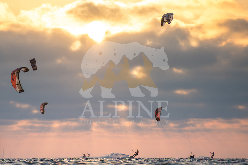 A group of outdoor athletes as seen kitesurfing on a sunny and windy evening at the North Sea, near the bay of Lauwersoog, Groningen, the Netherlands.