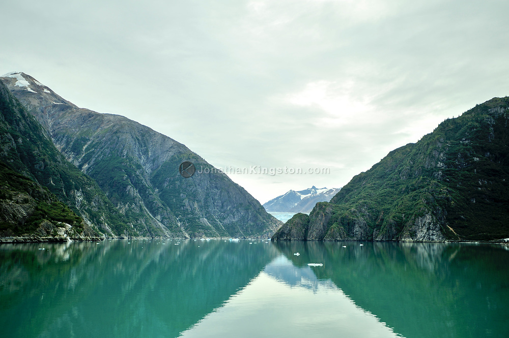 Magnificent cliffs reflect in the aqua green waters of Tracy Arm fjord near Juneau, Alaska.
