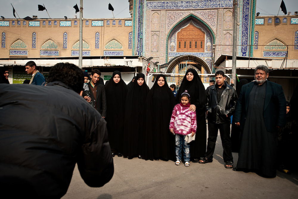 Iranian pilgrims pose for a family portrait by a street photographer outside the Kadhimiya Shrine in Baghdad, one of the holiest sites in Shia tradition.