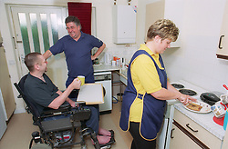 Carer cooking for wheelchair user in kitchen,