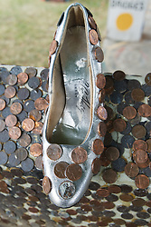 Shoe covered in pennies.  Heidelberg Project, Detroit, Michigan.  The Heidelberg Project is a grass roots project started by artist Tyree Guyton that uses art to help revitalize the embattled neighborhood.  Each year, over 275,000 people visit the project .  For more information, go to www.heidelberg.org