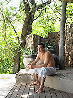 Mid adult man sitting on terrace barechested