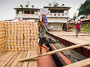 21 APRIL 2014 - CHIANG SAEN, CHIANG RAI, THAILAND: Burmese stevedores load juice and drinks made in Thailand onto a Chinese flagged river freighter in Chiang Saen, Chiang Rai province, Thailand. Chiang Rai province in northern Thailand is facing a drought this year. The 2014 drought has been brought on by lower than normal dry season rains. At the same time, closing dams in Yunnan province of China has caused the level of the Mekong River to drop suddenly exposing rocks and sandbars in the normally navigable Mekong River. Changes in the Mekong's levels means commercial shipping can't progress past Chiang Saen. Dozens of ships are tied up in the port area along the city's waterfront.      PHOTO BY JACK KURTZ