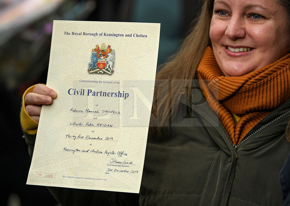 © Licensed to London News Pictures. 31/12/2019. London, UK. Rebecca Steinfeld holds up the couples Civil Partnership certificate as she and Charles Keidan Leave Kensington and Chelsea registry office following a mixed sex union ceremony. The couple took their fight to the Supreme Court to allow civil partnerships between heterosexual couples. Photo credit: Ben Cawthra/LNP