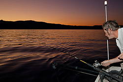 """Fishing Lake Tahoe at Sunset 1"" - This man was photographed fishing for Mackinaw on Lake Tahoe at sunset."