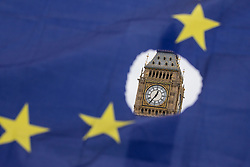 © Licensed to London News Pictures. 29/03/2017. London, UK. Big Ben is seen through a hole in the European Union flag shortly after the Prime Minister Theresa May's letter was delivered in Brussels. Photo credit: Rob Pinney/LNP