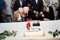 "PERDASDEFOGU, SARDINIA, ITALY - 30 JUNE 2013: Claudina Melis whispers something to her brother Antonio (94), while her sister Consolata (right, 106 years old) gesticulates, at her 100th birthday party in Perdasdefogu, Italy, on June 30th 2013.<br /> <br /> Last year, the Melis family entered the Guinness Book of World Records for having the highest combined age of any nine living siblings on earth — today more than 825 years. The youngest sibling, Mafalda – the ""little one"" – is 79 years old.<br /> <br /> The Melis siblings were all born in Perdasdefogu to Francesco Melis and Eleonora Mameli, who had a general store. Consolata, 106, is the oldest, then Claudia, 100; Maria, 98; Antonino, 94; Concetta, 92; Adolfo, 90; Vitalio, 87; Fida Vitalia, 81; and Mafalda, the baby at 79. Their descendants now account for about a third of the village."