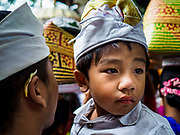 "02 AUGUST 2017 - UBUD, BALI, INDONESIA: A boy in his father's arms waits to get into the temple during the ""Merchants' Day"" ceremony at the Pura (Temple) Melanting Pasar Ubud, the small Hindu temple in the Ubud market. It's a day that merchants throughout Ubud come to the temple to make offerings and pray for prosperity.    PHOTO BY JACK KURTZ"