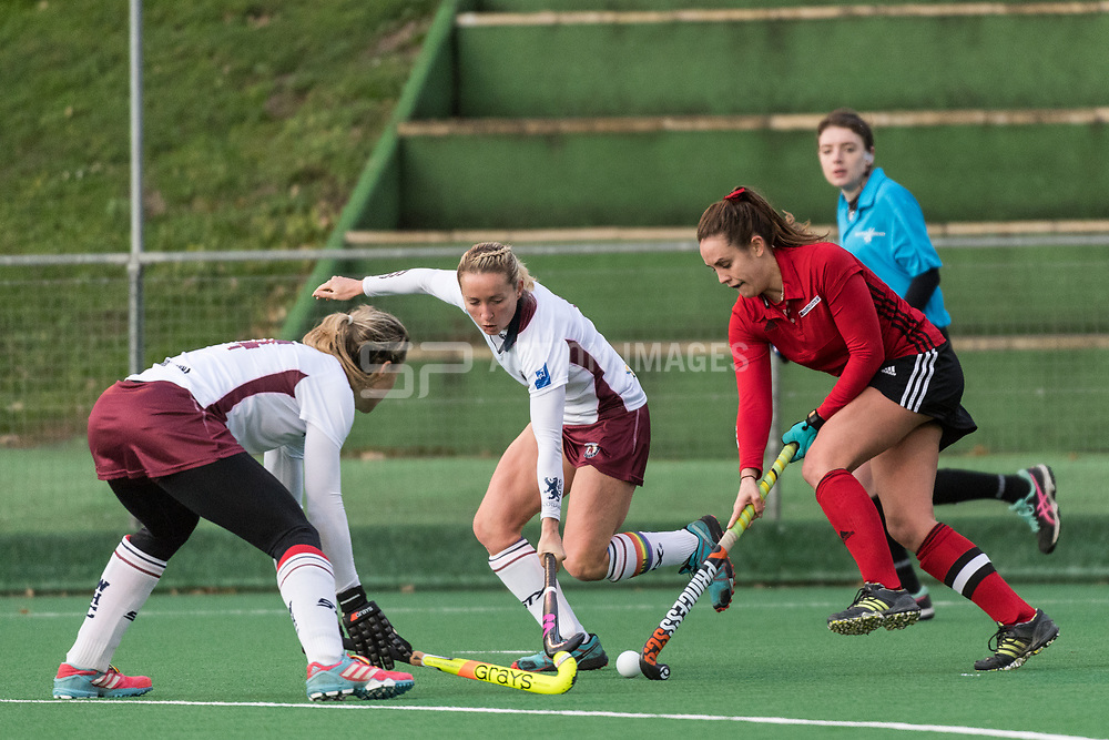Southgate's Caity Wales is tackled by Nikki Lloyd and Crista Cullen of Wimbledon. Southgate v Wimbledon - Investec Women's Hockey League East Conference, Trent Park, London, UK on 25November 2017. Photo: Simon Parker