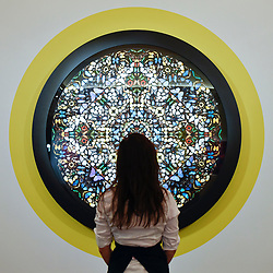 "© Licensed to London News Pictures. 14/09/2018. LONDON, UK. A technician views ""Epiphany"", 2005, by Damien Hirst (Est. GBP280,000-350,000) at a preview of the ""Yellow Ball: The Frank and Lorna Dunphy Collection"" sale at Sotheby's in New Bond Street.  Frank Dunphy was Damien Hirst's former business manager and mentor.  Over 200 works will be auctioned by Sotheby's on 20 September 2018.  Photo credit: Stephen Chung/LNP"