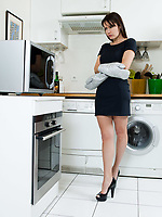 beautiful caucasian woman in a kitchen waiting with anxiety in front of the oven