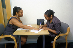Council housing officer and new tenant, signing contract, London UK