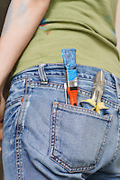 Woman with paintbrush and hand tools in back jeans pocket  mid section close-up