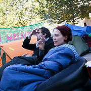 Activists staying warm in their sleeping bags outside their tents whilst talking. Day three of the occupation - and the first Monday.  The Occupy London Stock Exchange movement was formed in London in solidarity with the US based Occupy Wall Street. The movements are a respons and in anger to what is seen by many as corporate greed and a failed banking system being bailed out by the public, - which in return are suffering austerity measures to make up for the billions of lost money. The movement occupied the St Paul's Square in the City of London Sat Oct 15 after it failed to secure and occupy Pator Noster Square and the Stock Exchnage itself.