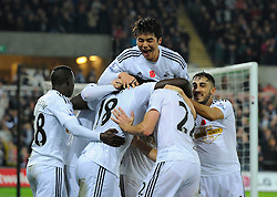 Swansea City's Bafetibis Gomis celebrates scoring the winning goal mobbed by team mates  - Photo mandatory by-line: Joe Meredith/JMP - Mobile: 07966 386802 - 09/11/2014 - SPORT - Football - Swanswa - Liberty Stadium - Swansea City v Arsenal - Barclays Premier League