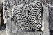 "Fragment of decorative Christian carving showing a diamond-shaped design with interlinked lines and floral and vegetal motifs, from the nave of the Basilica of St John, built 536-565 AD under Emperor Justinian on the site of the apostle's tomb, Ephesus, Izmir, Turkey. St John the Evangelist spent his last years in Ephesus and died here. In the 4th century a church was erected over his tomb but in the 6th century Justinian ordered the construction of a large, 6-domed basilica built of stone and brick with marble columns in a Greek cross plan, the ruins of which we see today. The church measures 130x56m and was an important Christian pilgrimage site, attaining the status of ""Church of the Cross"". Originally, the church interior would have been covered with frescoes, and the vaults with mosaics. An earthquake in the 14th century destroyed most of the building. Ephesus was an ancient Greek city founded in the 10th century BC, and later a major Roman city, on the Ionian coast near present day Selcuk. Picture by Manuel Cohen"
