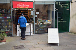 Queueing poster outside local wholefood shop open during Coronavirus lockdown in Norwich, UK April 2020. No one can enter the shop - requests are given to the staff through the counter at the door