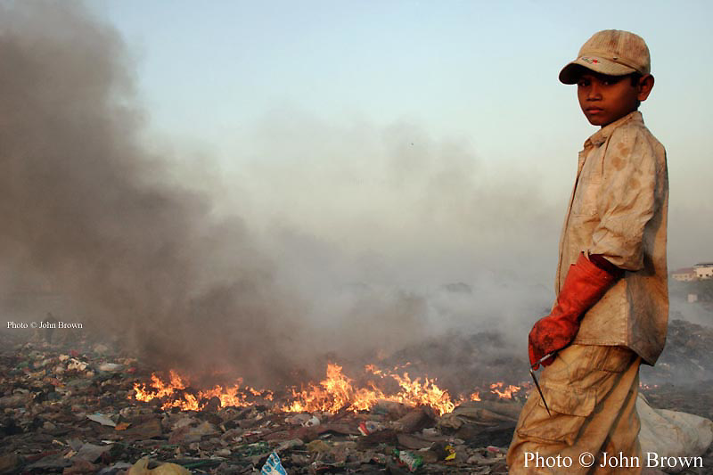 """A young boy who works as a scavenger stands neara pile of burning garbage at The Stung Meanchey Landfill in Phnom Penh, Cambodia. Fires spew noxious methane gas into the air and approximately 2000 people who scavenge here must endure these conditions daily to earn their livings. The dump is nicknamed """"Smokey Mountain""""."""