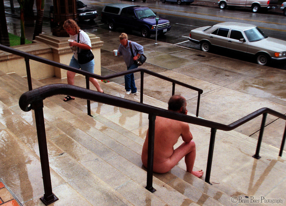 A naked man sits on the steps of the St. Patersburg City Hall.