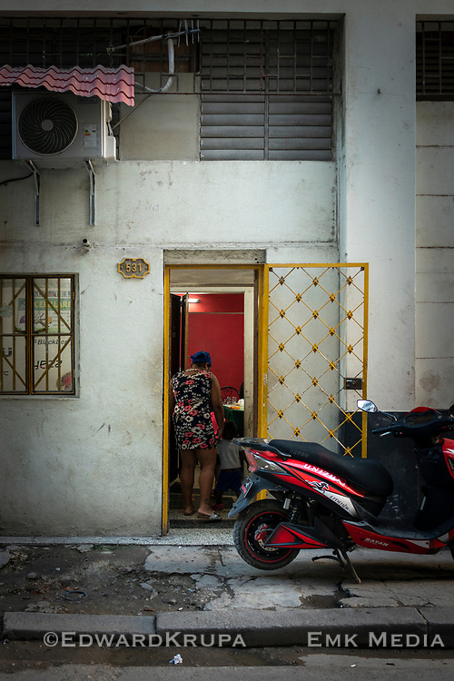 Mother and child entering a home with a yellow diamond patterned gate in Havana.