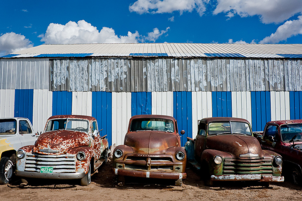 A row of Chevys in front of a striped wall under blue skies in a junkyard in Lamar, Colorado.