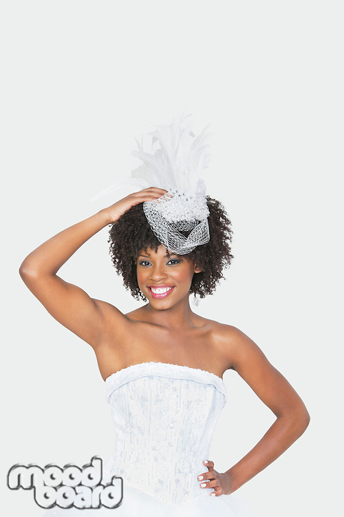 Portrait of an attractive African American bride wearing feather fascinator over gray background