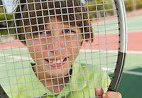Boy Looking Through Tennis Racket
