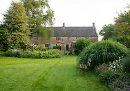 Herbaceous borders and lawn in front of Lower Severalls Farmhouse,  Crewkerne, Somerset, UK