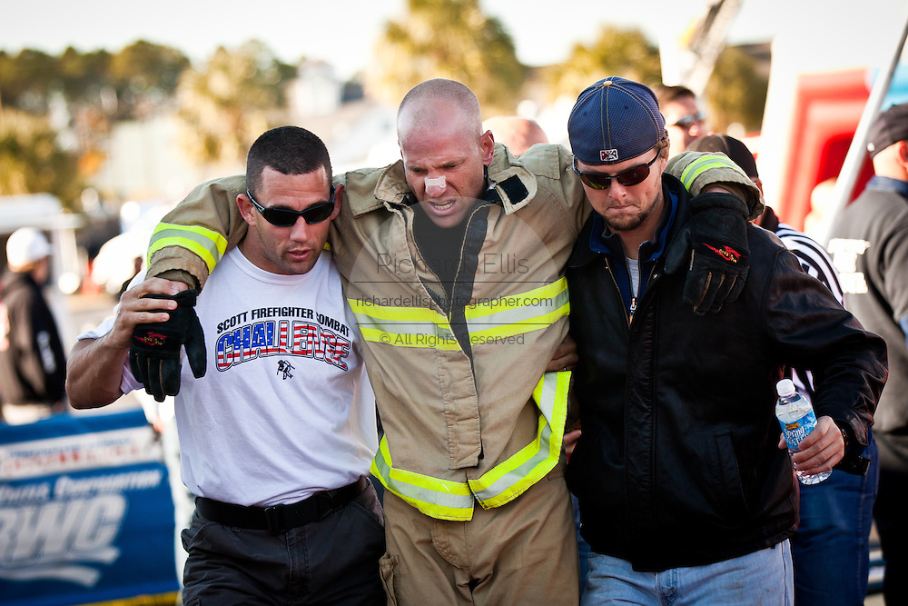 An exhausted firefighter is helped by officials after finishing the firefighting obstacle course d wearing full firefighting gear and working against the clock during the international finals of the Firefighter Combat Challenge on November 18, 2011 in Myrtle Beach, South Carolina.