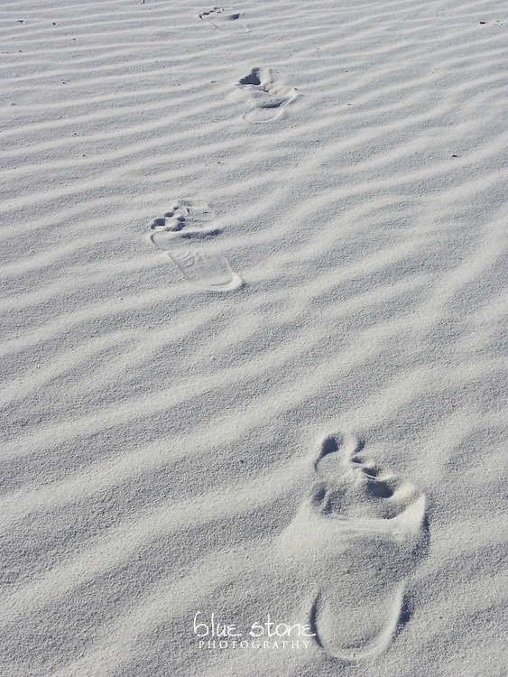 Human footprints in the white gypsum dunes leading out of the image.