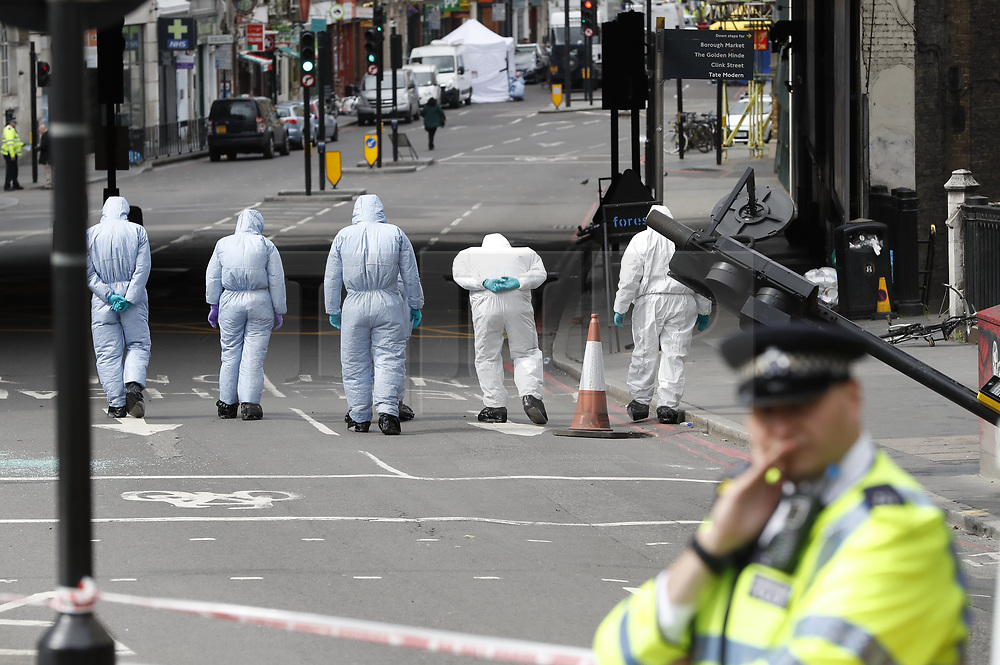 © Licensed to London News Pictures. 05/06/2017. London, UK.       Police and forensic officers at the scene at London Bridge in London following a terrorist attack in Saturday evening.   Three men attacked members of the public  after a white van rammed pedestrians on London Bridge.   Ten people including the three suspected attackers were killed and 48 injured in the attack. Photo credit: Peter Macdiarmid/LNP