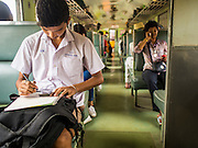 20 MARCH 2015 - KABIN BURI, PRACHINBURI, THAILAND: A teenager does classwork on a 3rd class train headed for Kabin Buri. The State Railways of Thailand (SRT), established in 1890, operates 4,043 kilometers of meter gauge track that reaches most parts of Thailand. Much of the track and many of the trains are poorly maintained and trains frequently run late. Accidents and mishaps are also commonplace. Successive governments, including the current military government, have promised to upgrade rail services. The military government has signed contracts with China to upgrade rail lines and bring high speed rail to Thailand. Japan has also expressed an interest in working on the Thai train system. Third class train travel is very inexpensive. Many lines are free for Thai citizens and even lines that aren't free are only a few Baht. Many third class tickets are under the equivalent of a dollar. Third class cars are not air-conditioned.   PHOTO BY JACK KURTZ