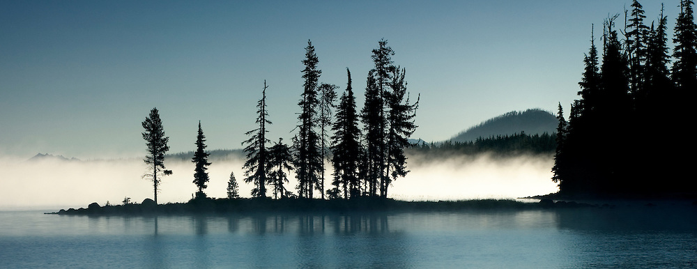 Lake effect fog is backlit by a clear autumn sunrise on Waldo Lake 1650m with Three Sisters volcanoes beyond (far left); Oregon Cascades.