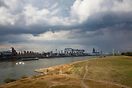 low water of the river Rhine, August 25, 2018, rain clouds above the dried up meadows on the river Rhine, view to the Rheinau harbor and the cathedral, Cologne, Germany.<br /> <br /> Niedrigwasser des Rheins, 25. August 2018, Regenwolken ueber den vertrockneten Poller Rheinwiesen, Blick zum Rheinauhafen und zum Dom, Koeln, Deutschland.