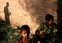 A Maoist rebel of the People?s Liberation Army takes a break as a young child looks on in a remote part of western Nepal on June 20, 2006. The ten-year old conflict in Nepal has claimed an estimated 13,000 lives. (Photo/Scott Dalton)
