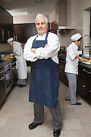 Chef stands with arms folded in blue apron and organised kitchen