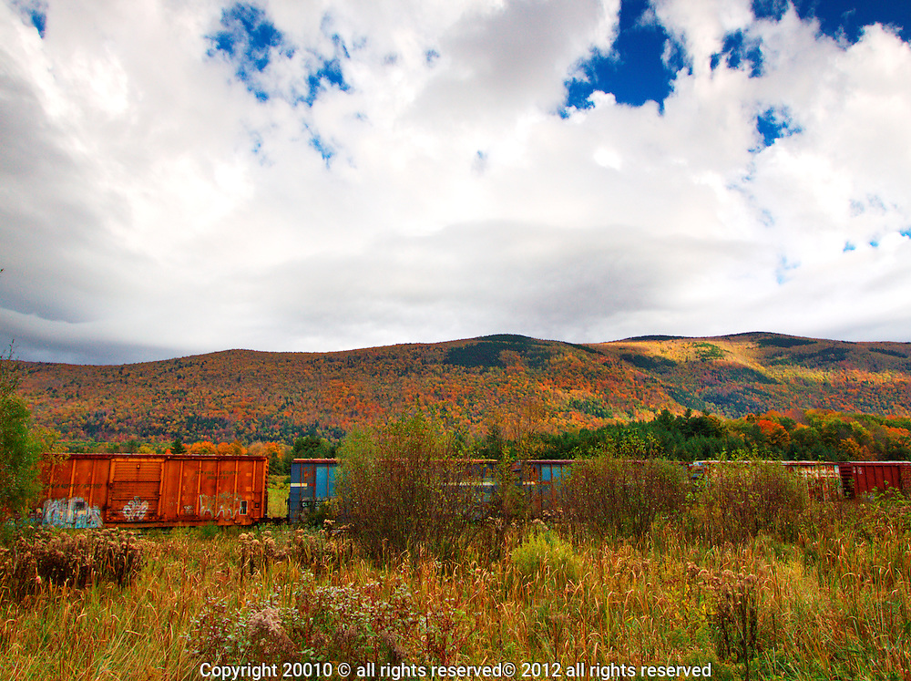 Colorful train in Fall, Danby, VT.  Colors of the rail cars compete with the foliage colors