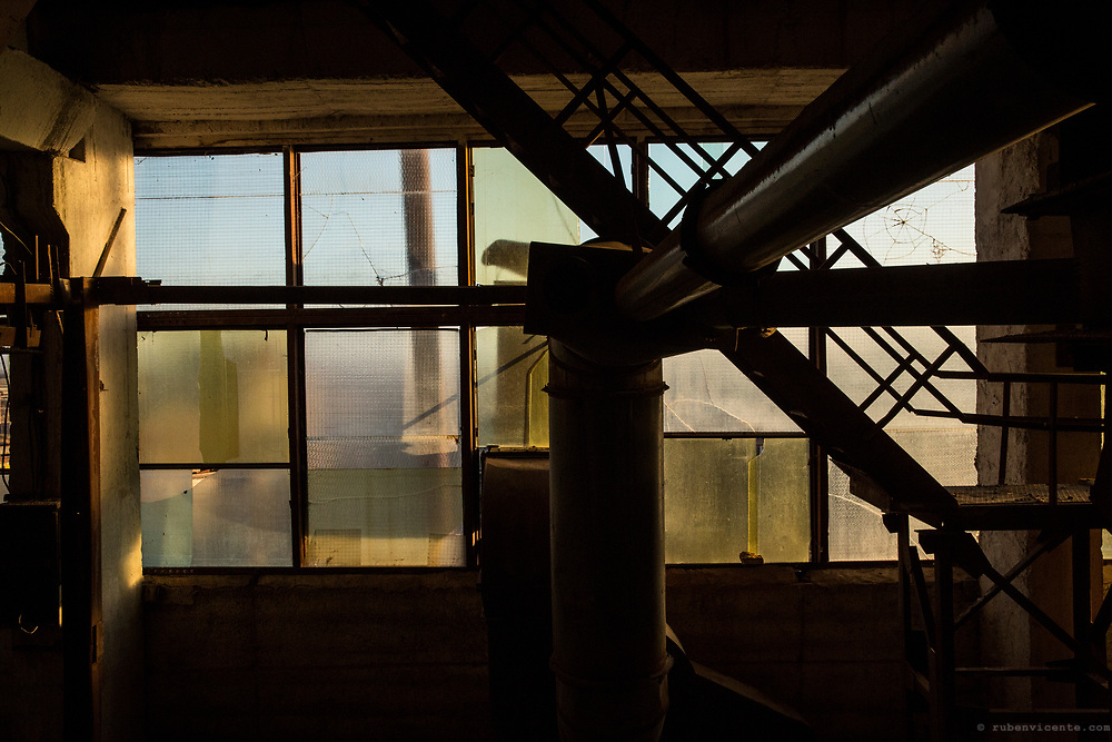 Pipes, stairs and colored window glass in an abandoned soviet era factory. Gyumri, Armenia
