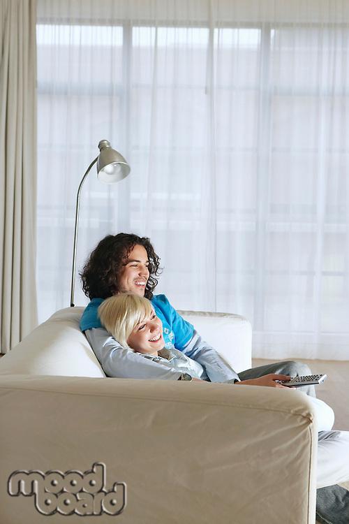 Boyfriend and girlfriend sitting on sofa watching television