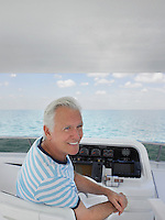 Middle-aged man sitting at helm of yacht smiling