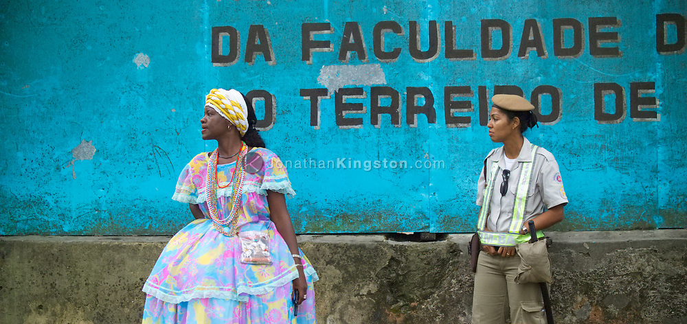 SALVADOR, BRAZIL - NOVEMBER 23:  A constable and woman in traditional Bahian dress stand in front of a blue wall in Salvador, Brazil on November 23, 2004.  This Bahian dress is in the style of candomble' priestesses.