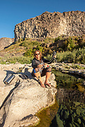 Woman filtering water from crystal clear spring pool along the Snake River canyon while camping near Twin Falls, Idaho.