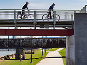 """01 APRIL 2020 - DES MOINES, IOWA: Bicyclists practice """"social distancing"""" while they cross a bridge over the Des Moines River on a warm spring day in downtown Des Moines. Despite the pleasant weather, many people stayed indoors because the coronavirus (SARS-CoV-2) pandemic. On Saturday morning, 04 April, Iowa reported 786 confirmed cases of the Novel Coronavirus (SARS-CoV-2) and COVID-19. There have been 14 deaths attributed to COVID-19 in Iowa. Restaurants, bars, movie theaters, places that draw crowds are closed until 30 April. The Governor has not ordered """"shelter in place"""" but several Mayors, including the Mayor of Des Moines, have asked residents to stay in their homes for all but the essential needs. People are being encouraged to practice """"social distancing"""" and many businesses are requiring or encouraging employees to telecommute.         PHOTO BY JACK KURTZ"""