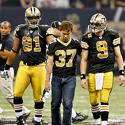 September 25, 2011; New Orleans, LA, USA; New Orleans Saints captains defensive end Will Smith (91) and quarterback Drew Brees (9) walk with former teammate Steve Gleason (37) who has been diagnosed with ALS, and served as the honorary captain before a game against the Houston Texans at the Louisiana Superdome. Mandatory Credit: Derick E. Hingle