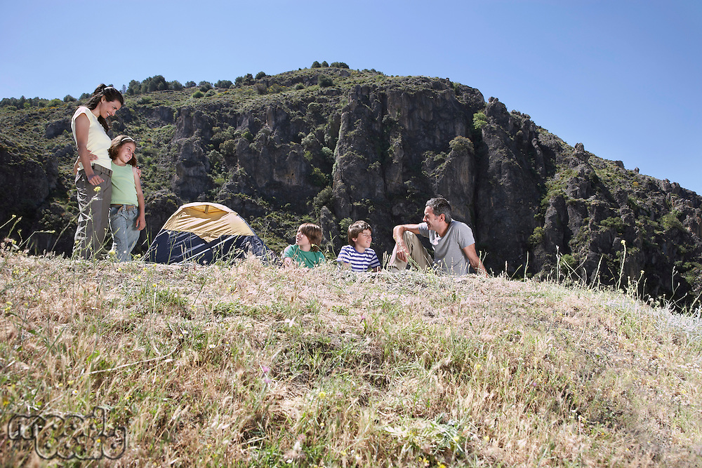 Family with three children (7-12) camping on mountain top