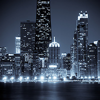 Photo of Chicago cityscape at night with the John Hancock Center building and other popular downtown Chicago skyline city buildings. The John Hancock Center is one of the world's tallest skyscrapers and is a famous fixture in the Chicago skyline.