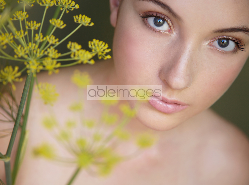 Young beautiful woman lost in thought with yellow flower