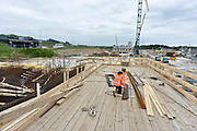 Nederland, Nijmegen, 15-5-2014 Aan de overkant van de Waal bij Nijmegen wordt druk gewerkt aan het creeren van een nevengeul in de rivier om bij hoogwater een betere waterafvoer te hebben. Het is een omvangrijk project waarbij onder meer de pijlers van het spoorviaduct een bredere basis moeten krijgen omdat die straks in de loop van het water staan. Ook de n325 die vanaf de Waalbrug naar Arnhem loopt moet over 400 meter opnieuw worden aangelegd omdat het talud vervangen wordt door pijlers. De weg wordt via een bypass omgeleid. Het dorp veurlent komt op een kunstmatig eiland te liggen. Inmiddels begint de nieuwe kade aan de noordkant van deze geul vorm te krijgen. Ruimte voor de rivier, water, waal. In de nieuwe dijk wordt een drempel gebouwd die stapsgewijs water doorlaat en bij hoogwater overloopt. Measures taken by Nijmegen to give the river Waal, Rhine, more space to flow during highwater. Foto: Flip Franssen/Hollandse Hoogte